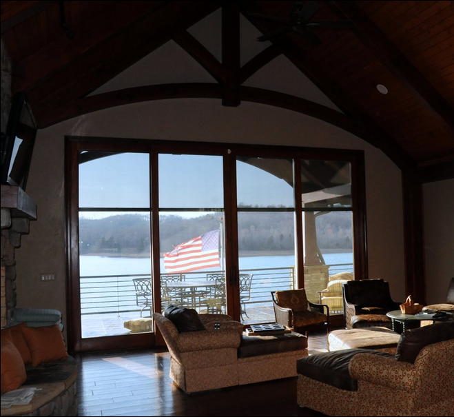 Living room with hard wood flooring and see thru stone fireplace. Cathedral ceilings with wood beams and wide open views of the lake and mountains