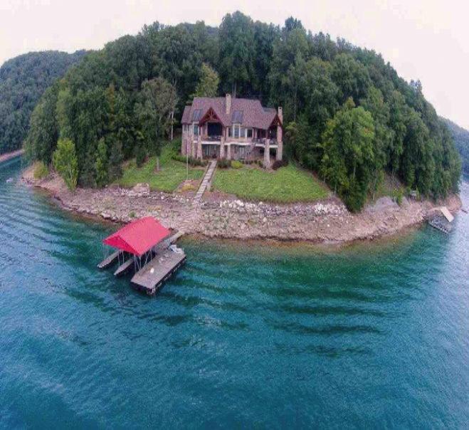 Another aerial lakefront view of the beautiful lake home surrounded by heavily wooded trees