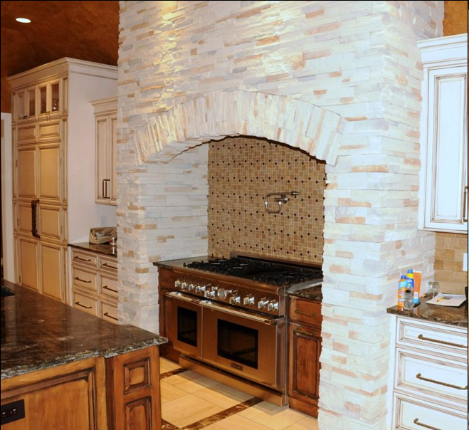 Thermador appliances including gas stove and range with tile backsplash and pot filler faucet