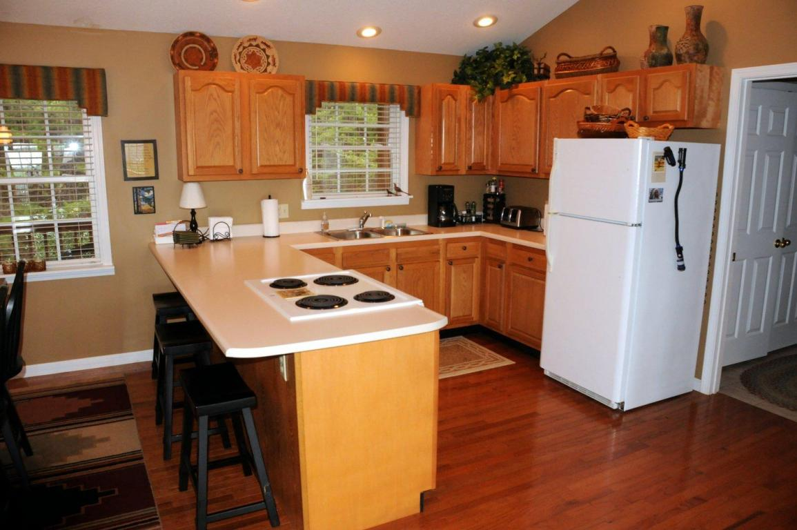 Kitchen with breakfast bar, hardwood floors, recessed lighting and all white appliances
