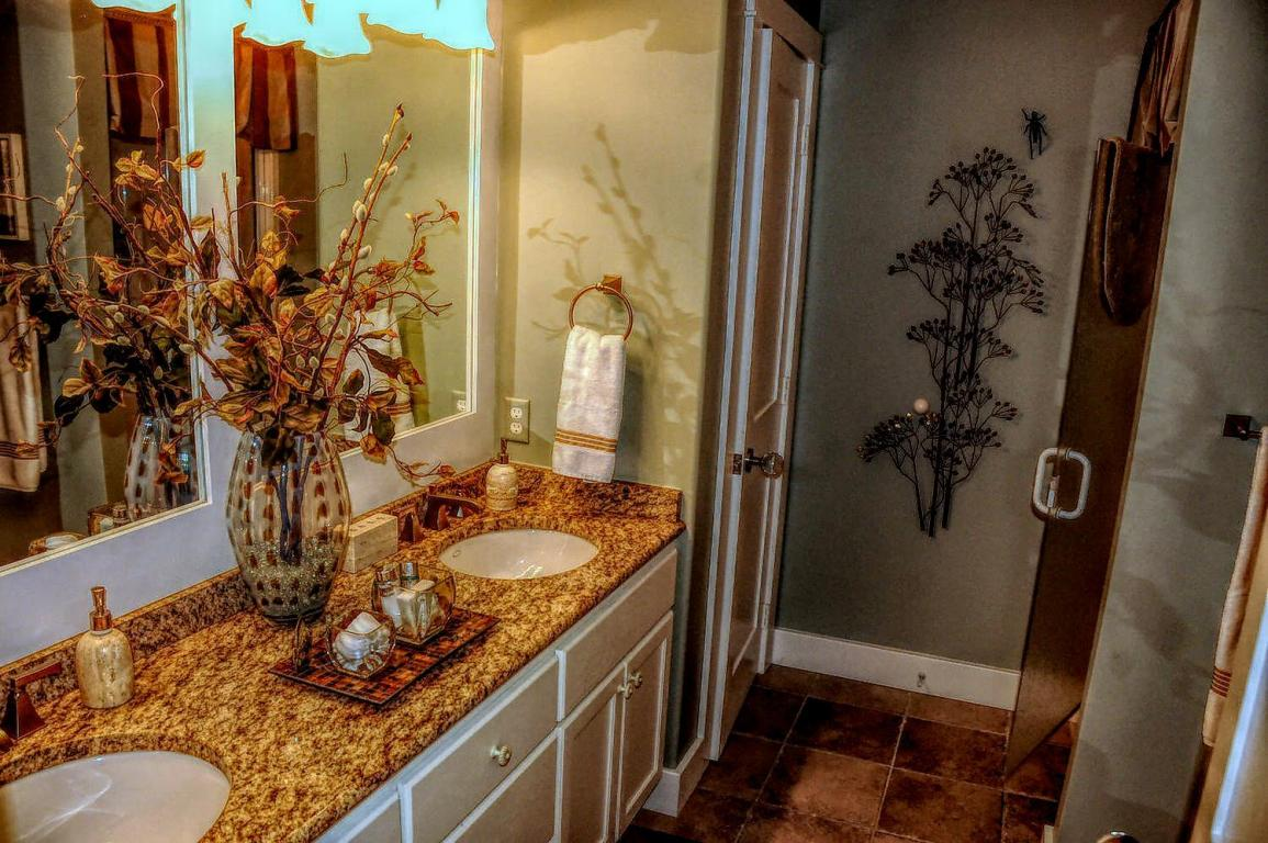 His and Her vanity sinks with Granite counter-tops, tile flooring and walk-in shower
