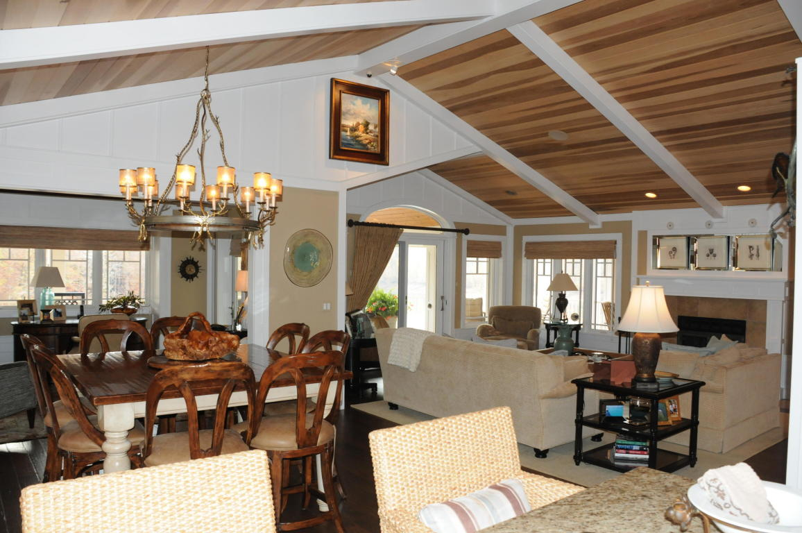 Gorgeous view of the dining room and living room with Tulip Popular wood ceilings, fireplace and designer lighting fixtures