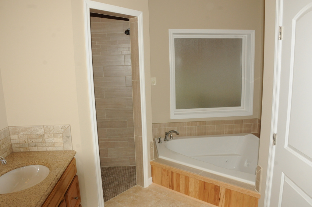 Master Bath with his/her vanity sinks, tile flooring, tile walk-in shower and jacuzzi spa
