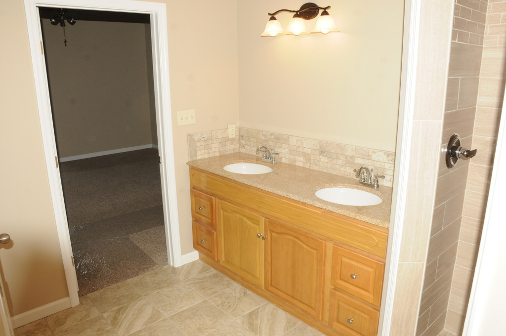 View of his/her vanity sinks with spacious cabinets and beautiful tile flooring