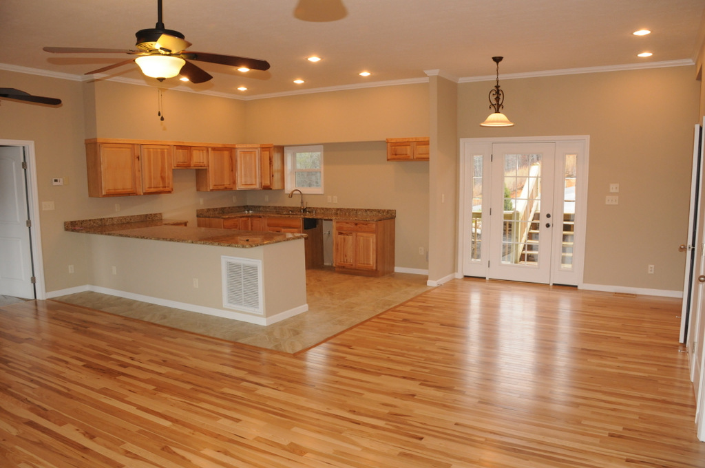 Spacious kitchen and dining room area with ceiling fans, crown molding and recessed lighting