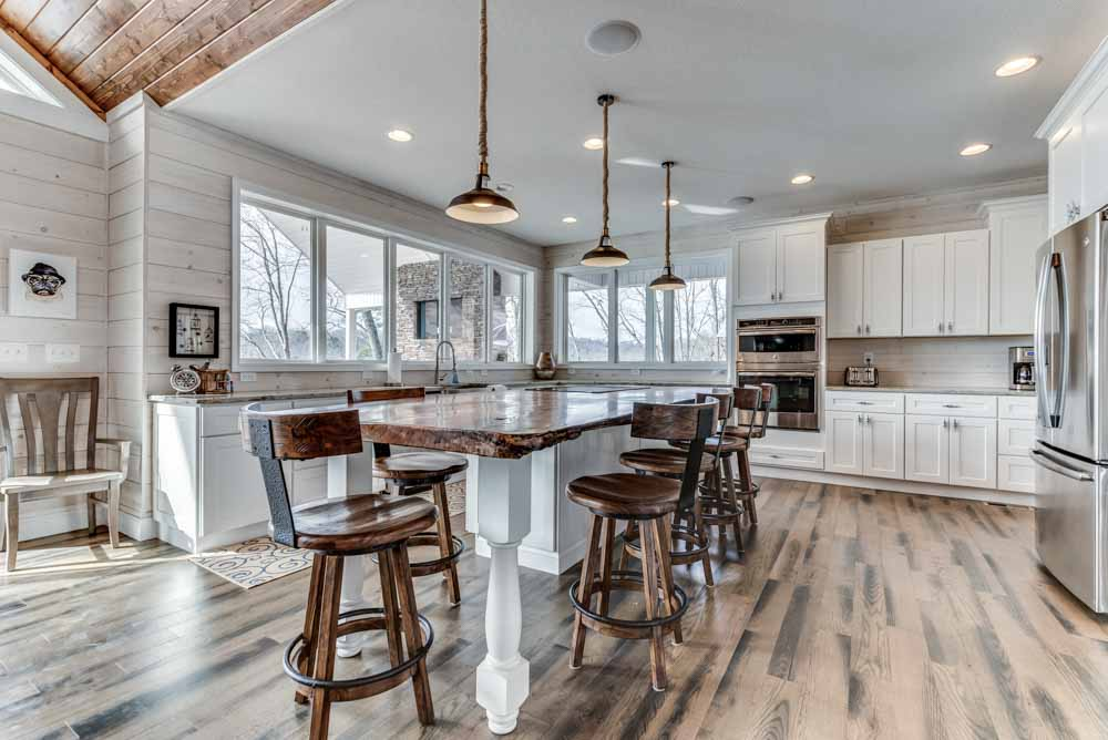 Fabulous kitchen view with white cabinets, all stainless steel appliances, custom island kitchen and more