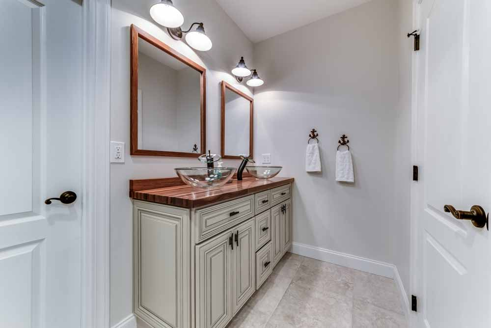 Master Bath with his/her vanity sink with bowl sinks, tile flooring and custom wood counter-top