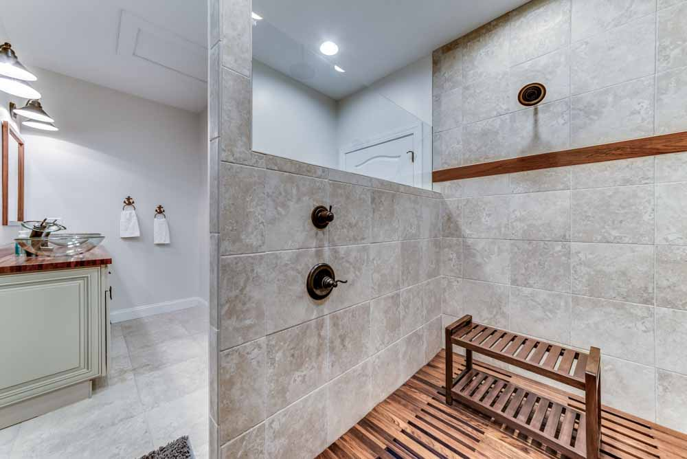 View of custom walk-in shower with tile and wood flooring
