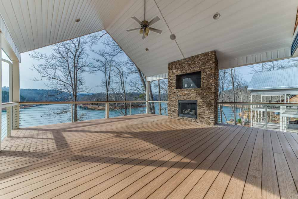 Spacious patio deck offering outdoor stacked stone fireplace with flat TV insert and plenty of views from every angle