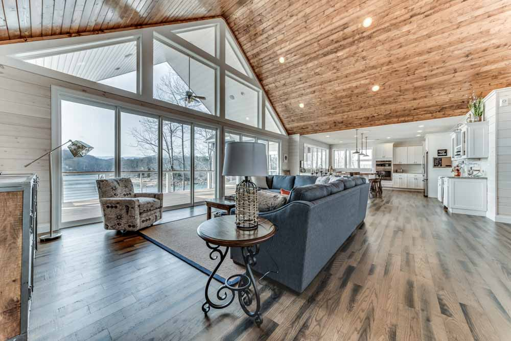 Living room view with an open floor plan, wood flooring and wide open views of the mountain and lakes