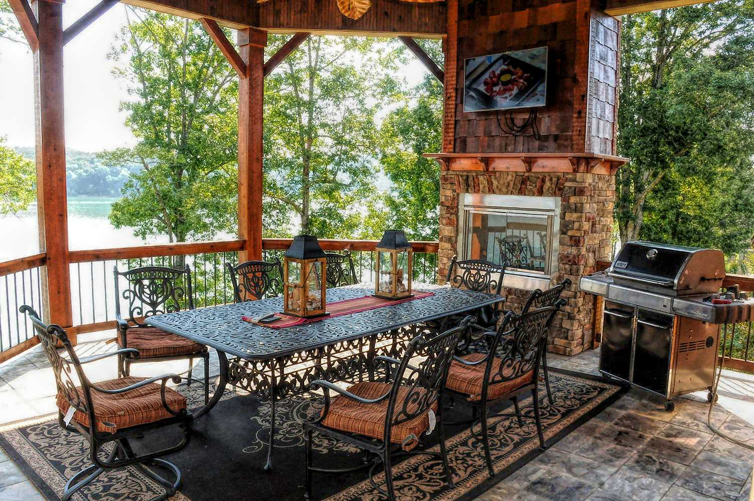 Patio view with outdoor stacked stone fireplace, ceiling fans at flat screen TV