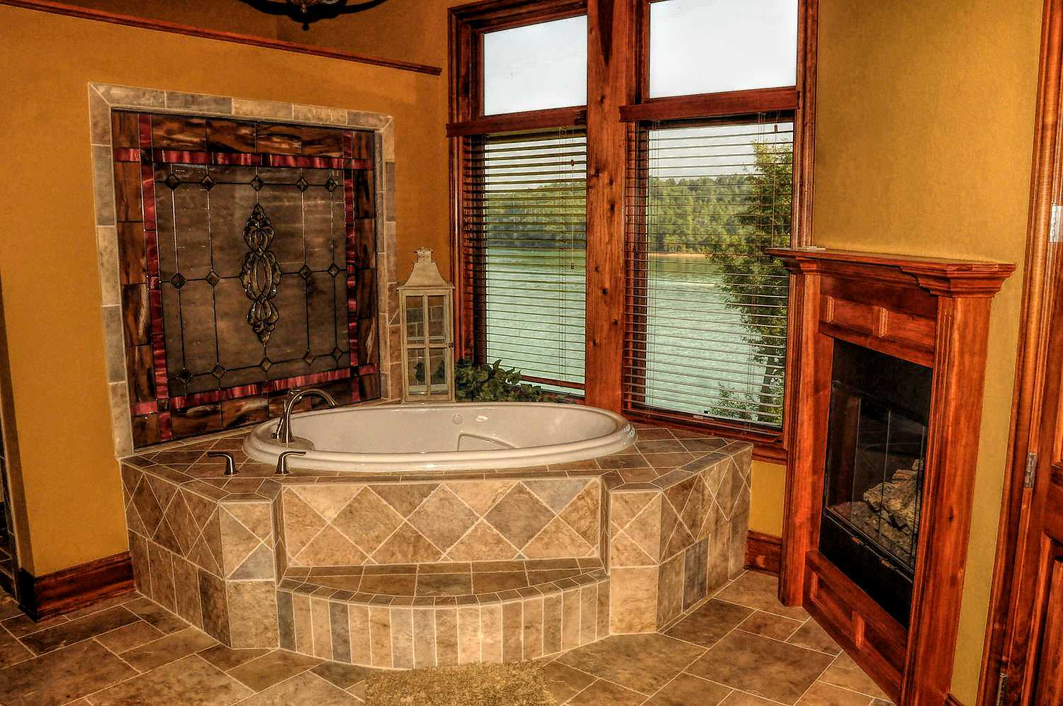 Master Bath with custom tile work, Jacuzzi and fireplace with great views of the lake