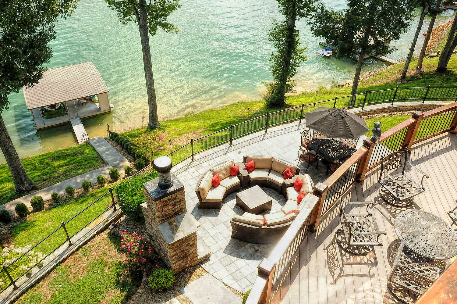 Grand view from the Master Bedroom balcony offering views of the stone fireplace patio area and boat dock