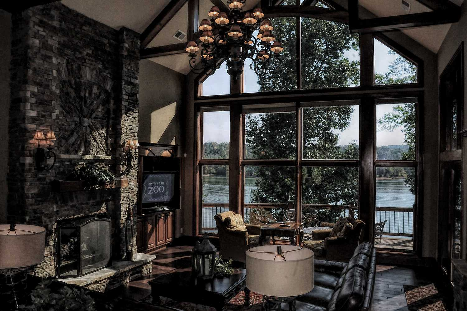 Gorgeous waterfront views from the living room with stacked stone fireplace and Cathedral ceilings